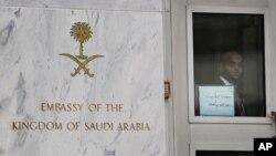 An embassy staffer peers through a glass door at an entrance of the Saudi Arabian embassy in Washington, DC, October 11, 2011.