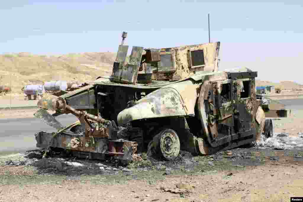 The wreckage of a destroyed Iraqi security forces vehicle lies on a road of Sulaiman Pek, north of Baghdad, June 13, 2014.