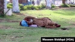 ایک شخص کراچی کے ایک سرکاری پارک میں آرام کر رہا ہے۔