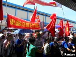 Workers wave Vietnamese national flags during an anti-China protest at a Chinese shoe factory in Vietnam's northern Thai Binh province, May 14, 2014.
