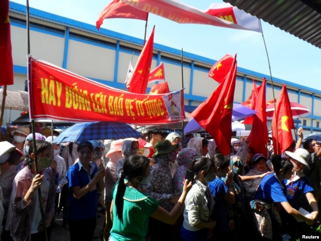 FILE - Workers wave Vietnamese national flags during an anti-China protest at a Chinese shoe factory in Vietnam's northern Thai Binh province, May 14, 2014. Thousands of Vietnamese set fire to foreign factories and rampaged in industrial zones in the south of the country in an angry reaction to Chinese oil drilling in a part of the South China Sea claimed by Vietnam, officials said.
