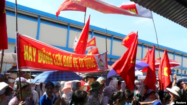 FILE - Workers wave Vietnamese national flags during an anti-China protest at a Chinese shoe factory in Vietnam's northern Thai Binh province, May 14, 2014.