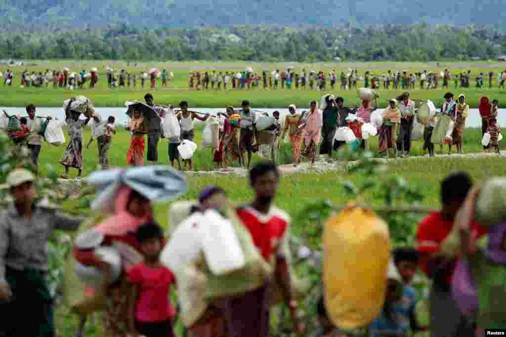 Para pengungsi Rohingya yang baru datang dari Rakhine, Myanmar, memasuki Palang Khali, Bangladesh, setelah militerBangladesh memberikan izin kepada mereka untuk memasuki negara itu.
