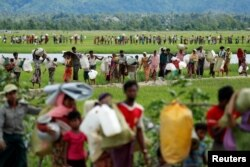 FILE - Rohingya refugees, who crossed the border from Myanmar two days before, walk after they received permission from the Bangladeshi army to continue on to the refugee camps, in Palang Khali, near Cox's Bazar, Bangladesh, Oct. 19, 2017.
