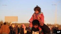 مشرقی حلب سے جانے والا ایک شہری اپنی بچی کو کندھوں پر اٹھائے ہوئے ہے۔ 15 دسمبر 2016