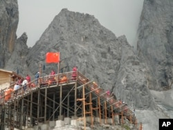 This Sept. 22, 2018 photo shows tourists visiting the Baishui Glacier No.1 atop of the Jade Dragon Snow Mountain in the southern province of Yunnan in China home. Scientists say the glacier is one of the fastest melting glaciers in the world due to climate change and its relative proximity to the Equator. It has lost 60 percent of its mass and shrunk 250 meters since 1982. (AP Photo/Sam McNeil)