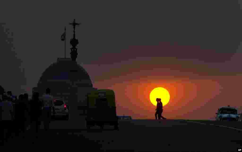 در دهلی نو مردم در غروب آفتاب به سمت خانه میروند. خورشيد در پشت قصر رياست جمهوری هند ديده میشود.