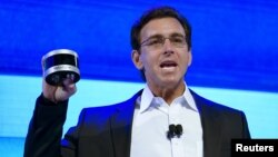 FILE - Ford Motor Co. CEO Mark Fields holds up a new Velodyne LiDAR sensor at a news conference at the Consumer Electronics Show in Las Vegas, Jan. 5, 2016.