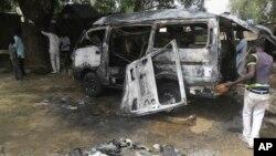 Warga memeriksa kendaraan yang hancur akibat ledakan di Potiskum, Nigeria, Selasa (24/2).