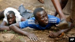 Men duck for cover as heavy gunfire erupts in the Miskin district of Bangui. (Feb. 3, 2014.)