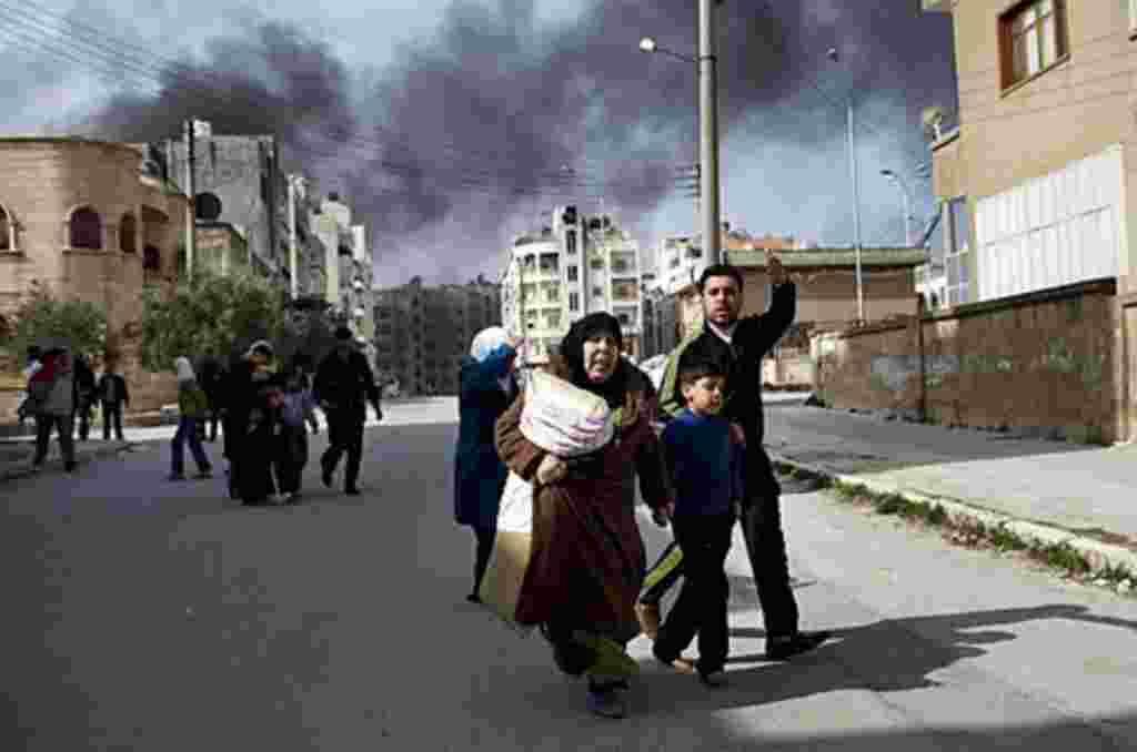 Una familia escapa de una batalla entre el Ejército de Liberación Siria y tropas del gobierno en Idlib, al norte de Siria.