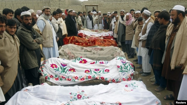 Villagers stand around the bodies of girls who were killed by an explosion in Jalalabad, Afghanistan, December 17, 2012.
