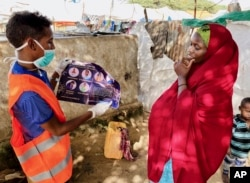 In this photo taken Wednesday, June 10, 2020, an internally-displaced Somali woman, right, is informed how to protect herself from the coronavirus, at the Weydow IDP camp in Mogadishu, Somalia. (Hamza Osman/International Organization for Migration (IOM)