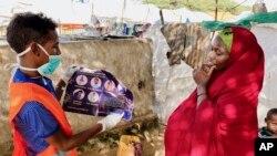 Seorang perempuan Somalia diberi tahu bagaimana melindungi dirinya dari virus corona, di kamp IDP Weydow di Mogadishu, Somalia. (Hamza Osman/International Organization for Migration via AP)