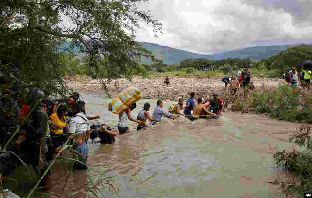 Migrants use a rope to cross the Tachira River, the natural border between Colombia and Venezuela, as the official border remains closed because of the COVID-19 pandemic in Cucuta, Colombia, November 19, 2020.