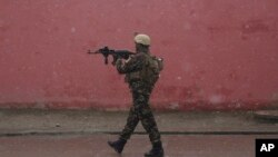 A member of Afghan security personnel arrives at the site of an attack at a military academy in Kabul, Afghanistan, Jan. 29, 2018. Afghan security forces arrested eight militants after members of the Islamic State group attacked a military academy in Kabul.