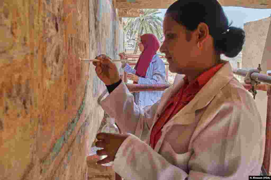 Two female Egyptian archaeological workers, Mervat and Fatma, restore the colors on the walls of Karnak temple in Luxor, Egypt, April 20, 2018.
