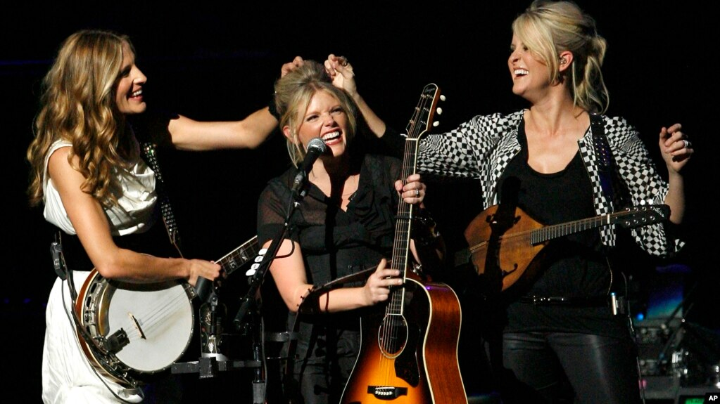 FILE - In this Oct. 18, 2007 file photo, Emily Strayer, left, and Martie Maguire, right, adjust Natalie Maines' hair as the Dixie Chicks perform at the new Nokia Theater in Los Angeles. The group have dropped the word dixie from their name and are now going by The Chicks. (AP)