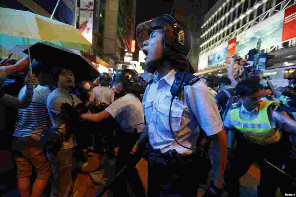 A riot policeman yells during a confrontation with protesters at Mongkok shopping district in Hong Kong. Police used pepper spray and charged toward the protesters with batons on Friday evening as tension escalated.