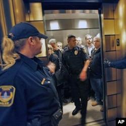 批准取消政府员工集体谈判权议案的共和党人在执法人员陪同下走出议会