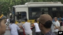 In this image made from video, a protester is dragged to a bus by police officers during an anti-China rally near Chinese Embassy in Hanoi, Vietnam, July 10, 2011