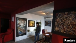 A visitor views artwork at The Venue art gallery in Kabul December 2, 2012.