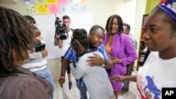 Pierrot Mervillier, tengah belakang, memeluk seorang anak perempuan yang tidak diungkap identitasnya, setelah keluarganya berbicara kepada media, 22 Mei 2017, di Miami. Anak perempuan Haiti itu tinggal di Amerika dengan Status Terlindungi Sementara. (Foto:Dok)