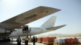 FILE - Airport workers load the first cargo plane after the Afghanistan-India air corridor inauguration ceremony at Hamid Karzai International Airport in Kabul, Afghanistan, June 2017.