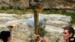 Ngọn lửa Olympic được vị nữ tu trao cho người rước đuốc đầu tiên (vận động viên huy chương bạc Olympic của Hy Lạp Spyros Gianniotis), ngày 10 tháng 5, 2012
