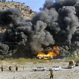 Residents look at burning oil tankers carrying fuel supplies for NATO forces, caused by a militant attack near Jamrud, in the Khyber tribal region along the Afghan border, 20 Dec 2010