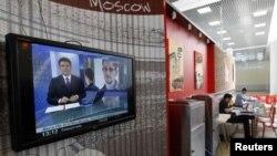Un noticiero de tv visto en una cafetería del aeropuerto de Moscú con información sobre Edward Snowden.