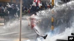 Un manifestante patea una contenedor de gas lacrimógeno en Bogotá.