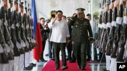 Philippine President Rodrigo Duterte, center left, salutes the troops with Armed Forces Chief Gen. Ricardo Visaya before boarding his flight for a three-day official visit to Japan at the Ninoy Aquino International Airport in suburban Pasay city, south of