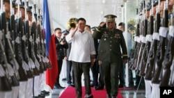 2016年10月25日,菲律宾总统杜特尔特(中左)向军队敬礼,之后他登机前往日本进行为期三天的国事访问。