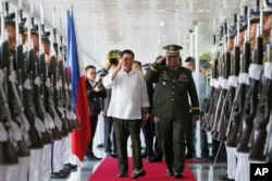 FILE - Philippine President Rodrigo Duterte, center left, salutes the troops with Armed Forces Chief Gen. Ricardo Visaya before boarding his flight for a three-day official visit to Japan.