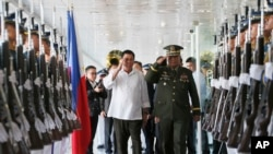 Philippine President Rodrigo Duterte, center left, salutes the troops with Armed Forces Chief Gen. Ricardo Visaya before boarding his flight for a three-day official visit to Japan at the Ninoy Aquino International Airport in suburban Pasay city, south of Manila, Philippines, Tuesday, Oct. 25, 2016.
