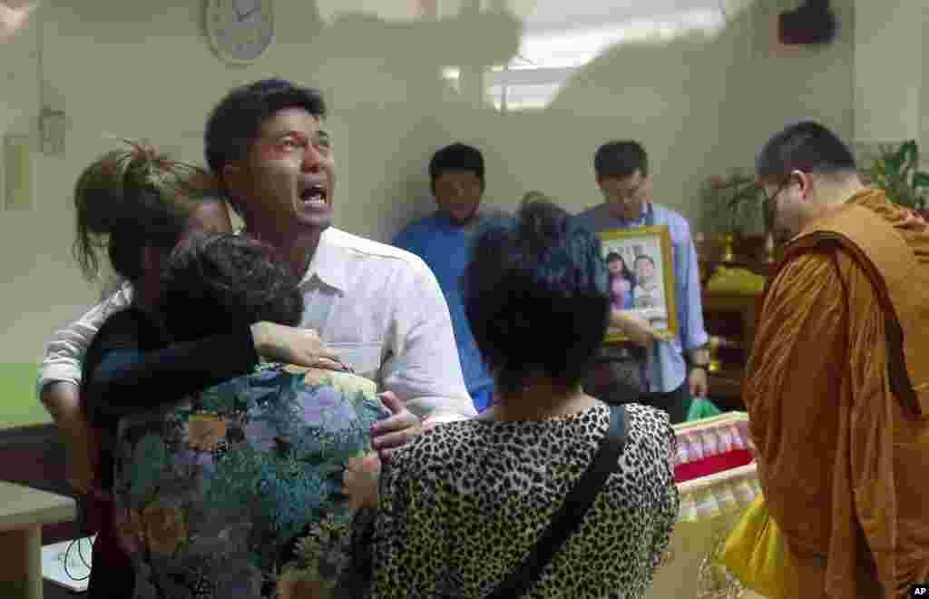 Tayakorn Yos-ubon, ayah dua anak-anak yang tewas dalam serangan bom Minggu (23/2) terhadap lokasi demonstrasi anti-pemerintah, dipeluk oleh keluarganya dalam upacara di sebuah rumah sakit di Bangkok. (AP/Wason Wanichakorn)