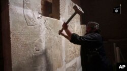 FILE - This image made from video posted on a militant social media account affiliated with the Islamic State group, April 11, 2015, purports to show a militant taking a sledgehammer to an Assyrian relief at the site of the ancient Assyrian city of Nimrud, which dates to the 13th century B.C.