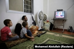 FILE - A Free Syrian Army fighter watches U.S. President Barack Obama's speech with his family in Ghouta, Damascus August 31, 2013.