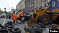 FILE - Municipal workers remove tires as they dismantle barricades set up during the protests that toppled Moscow-backed president Viktor Yanukovych in central Kyiv, July 1, 2014.