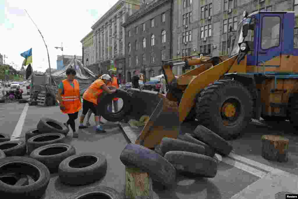 Municipal workers remove tires as they dismantle barricades set up during the protests that toppled Moscow-backed president Viktor Yanukovych in central Kyiv, July 1, 2014.