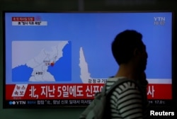 A passenger walks past a TV broadcasting a news report on North Korea's failed missile launch from its east coast, at a railway station in Seoul, South Korea, April 16, 2017.