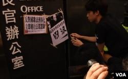 示威者將反對中國《國歌法》立法聯署聲明及抗議標語貼在特首辦公室入口外。(美國之音湯惠芸)