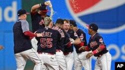 Peloteros de los Indios de Cleveland celebran el imparable de Jay Bruce que permitió la carrera que dio al equipo la vigésima segunda victoria consecutiva en la temporada, un hito en la historia del béisbol de las Grandes Ligas.