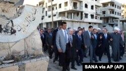 Presiden Suriah Bashar Assad (tengah) berjalan seusai sholat Idul Adha di Daraya, Suriah, 12 September 2016 (SANA via AP).