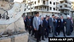 Foto divulgada por la agencia estatal de noticias siria, SANA, del presidente Bashar al Assad, centro, en los suburbios de Daraya, Damasco.