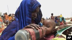 FILE - A mother quenches her malnourished child's thirst while waiting for food handouts at a health center in drought-stricken remote Somali region of Eastern Ethiopia, also known as the Ogaden, July 2011.