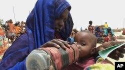 Seorang ibu memberi minum anaknya sementara menunggu pembagian makanan di Ogaden, Somalia. (Foto: Dok)