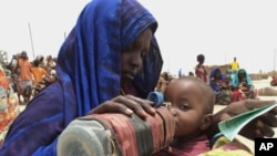 A mother quenches her malnourished child's thirst while waiting for food handouts at a health center in Ethiopia. File.