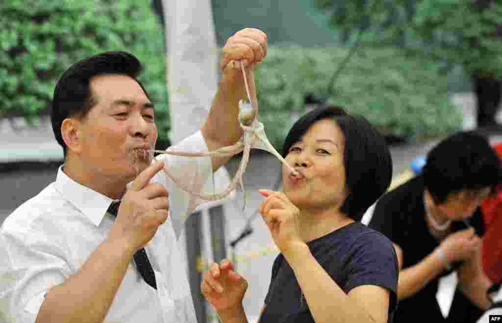 A South Korean man and a woman eat a live octopus during an event to promote a local food festival in Seoul.